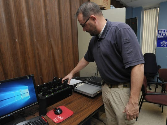 Detective Pete Shaw demonstrates how the body cameras connect to the docking station Thursday at the Chillicothe Police Department. The department is getting new cameras after the current ones kept breaking.