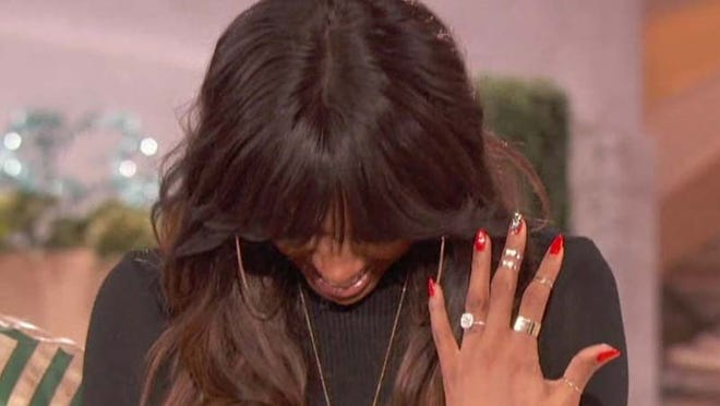 Kelly Rowland puts her head down and laughs as she shows off her engagement ring on Wednesday's 'Queen Latifah Show.'