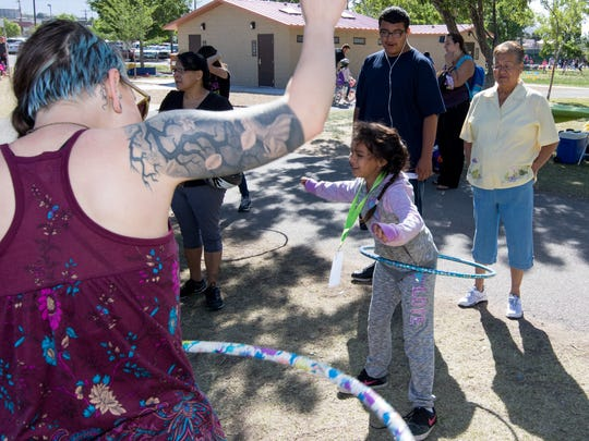 Angelica Campolla mastering the hula hoop as Stephanie Midwood of the Branigan Library encourages her at the KidFit event held Saturday at Young Park.