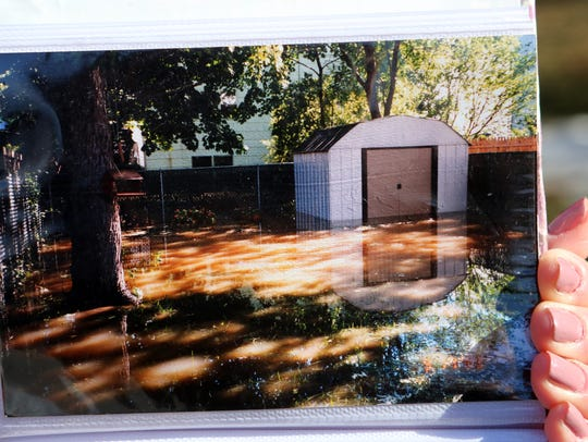 Ann Marie Geraci shows a 1999 photo from flooding after