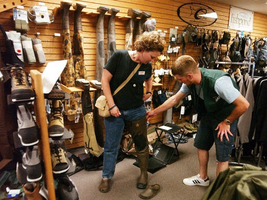 Shelly Whipple tries on a pair of hip waders at Jax