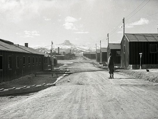 Man standing on the road between barracks  in lower