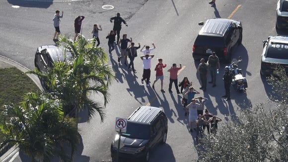 People are brought out of the Marjory Stoneman Douglas High School after a shooting.  Credit: Joe Raedle/Getty Images