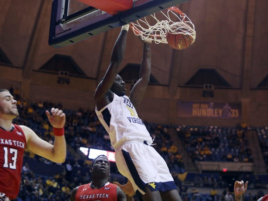 West Virginia forward Lamont West (15) dunks while defended by Texas Tech guard Matt Mooney (13) during the second half of an NCAA college basketball game Wednesday, Jan. 2, 2019, in Morgantown, W.Va. Texas Tech defeated West Virginia 62-59. (AP Photo/Raymond Thompson)