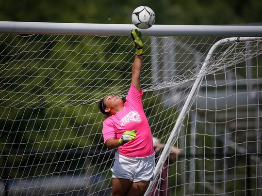 Ankeny Centennial senior goal keeper Marissa Lopez swats a shot away from the net against Ankeny during the Class 3A championship game of the 2018 Iowa girls high school state soccer tournament in Des Moines on Saturday, June 9.