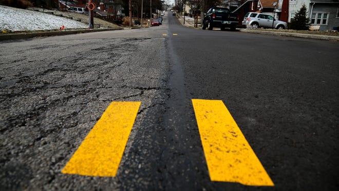 Cypress way is split in half between Cincinnati and Norwood, as evidenced by one half of the street being freshly repaved while the other is in need of repair in Norwood, Ohio, on Friday, Feb. 10, 2017.