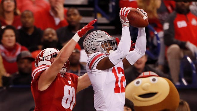 Ohio State Buckeyes cornerback Denzel Ward (12) intercepts a pass intended for Wisconsin Badgers tight end Troy Fumagalli (81) during the first quarter in the Big Ten championship game at Lucas Oil Stadium.