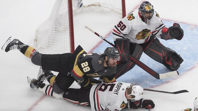 Vegas Golden Knights' William Carrier (28) and Chicago Blackhawks' Connor Murphy (5) battle as Blackhawks goalie Corey Crawford (50) looks for the puck during the third period of an NHL hockey Stanley Cup first-round playoff series, Thursday in Edmonton, Alberta.