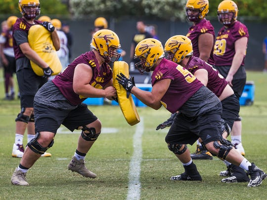 Offensive linemen Jesse Cozens, 62, left, and Tyson Rising, 58, right, collide on the line during practice with the Arizona State Sun Devils in Tempe, Thursday, April 12, 2018.