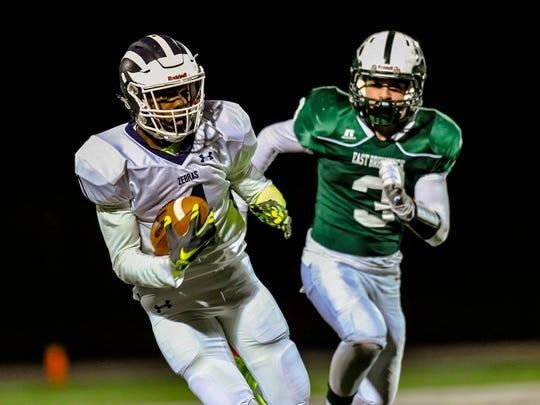 New Brunswick's Kadas Reams catches a 35-yard touchdown pass in front of East Brunswick's Jack Solimini in the first quarter on Nov. 4, 2016.