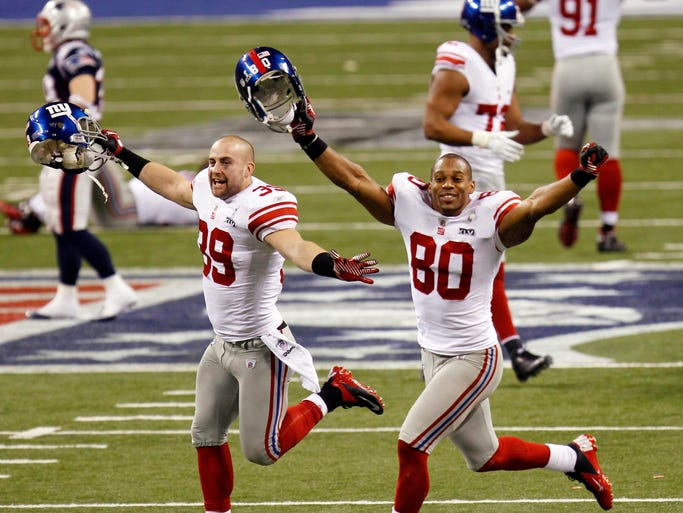 Feb 5, 2012; Indianapolis, IN, USA; New York Giants defensive back Tyler Sash (39) and wide receiver Victor Cruz (80) celebrate after Super Bowl XLVI against the New England Patriots at Lucas Oil Stadium.  Mandatory Credit: Tim Farrell/THE STAR-LEDGER via USA TODAY Sports