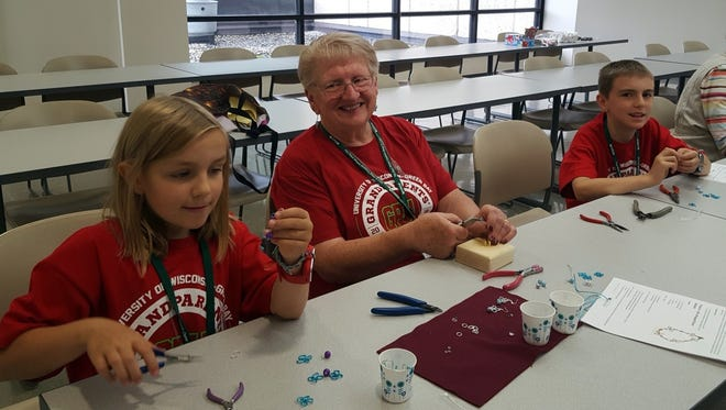 Arianna, Grandma Susan, and Eli work at UWGB Grandparents' University Jewelry Making