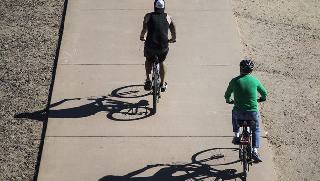 Shadows of bicycle riders are cast on the sidewalk alongside Tempe Town Lake on Feb. 5, 2017.