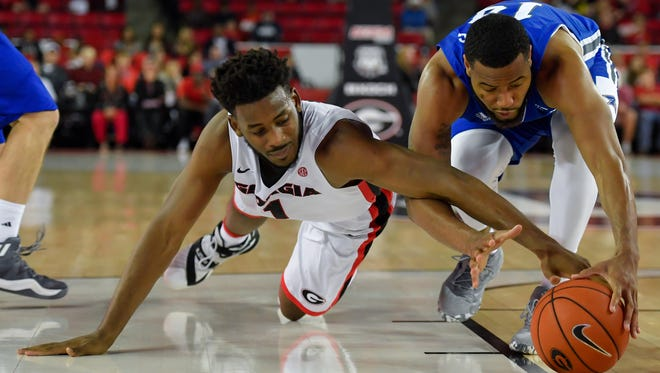 UNC Asheville's Ahmad Thomas, right, goes low in an attempt to take the ball away from Georgia's Yante Maten (1).