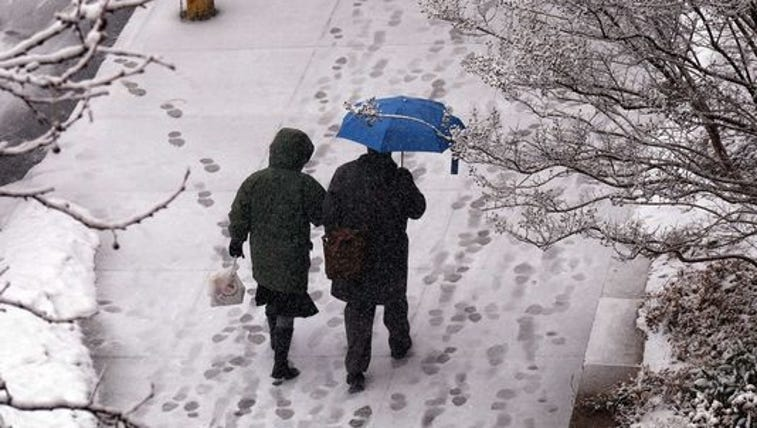 A couple walk along a residential area during a winter
