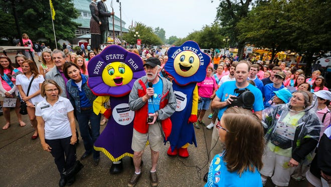 Jerome Thompson, center, State Curator & Historic Sites Administrator, leads spectators and State Fair Queen contestants participate in a 1K Historical Walk at the 2014 Iowa State Thursday Aug. 7, 2014 in Des Moines, Iowa the fair runs Aug. 7- Aug. 17.