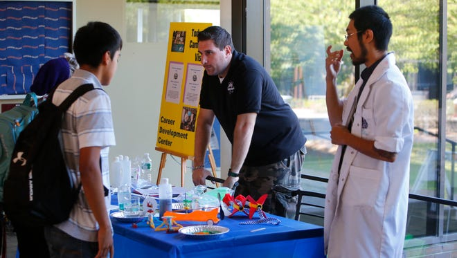 Mad Science job recruiters Ron Sosinski and Q Tomaru talk with students at Purchase College during a recruitment drive at the school on Sept. 15. The company was looking to hire young adults with performance skills for science programs for children that combine facts with fun.