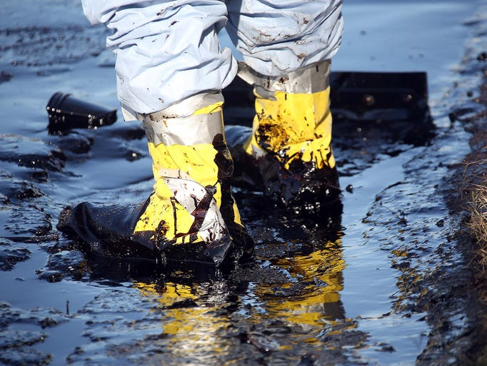 A worker mops up crude oil May 15 in the Atwater Village section of Los Angeles. A day earlier, a high-pressure pipe burst, spilling 10,000 gallons of crude oil onto Los Angeles streets and buildings.