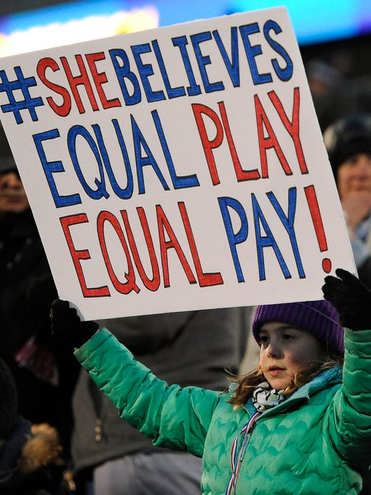 A girl holds up a sign for equal pay for the U.S. women soccer players, during the first half of an international friendly soccer match between the United States and Colombia on Wednesday, April 6, 2016, in East Hartford, Conn. (AP Photo/Jessica Hill)