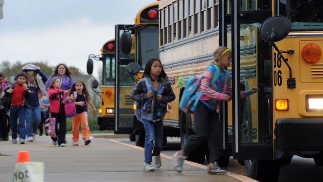 Students from Bunker Hill Elementary walk out to their assigned buses following school in Indianapolis.