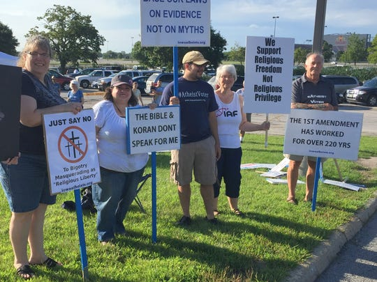 Atheists tote signs Saturday outside The Family Leader Summit in Ames, Iowa