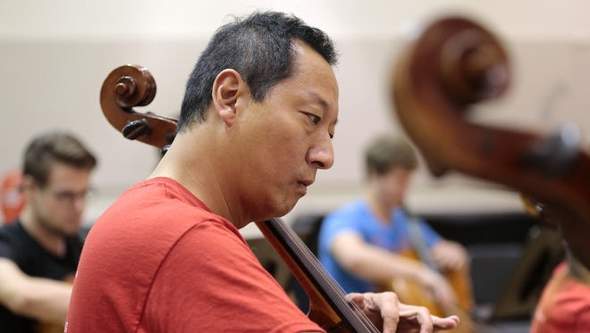 University president Santa Ono practices with fellow cellists during a practice session in a rehearsal room at the College Conservatory of Music on the University of Cincinnati campus in Cincinnati, Ohio, on Friday, Aug. 28, 2015.