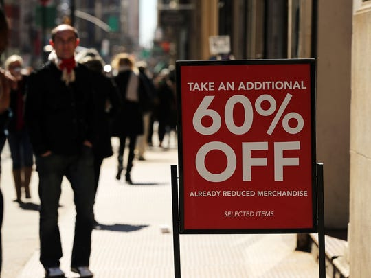 A clothing sale sign stands outside of a store in Manhattan