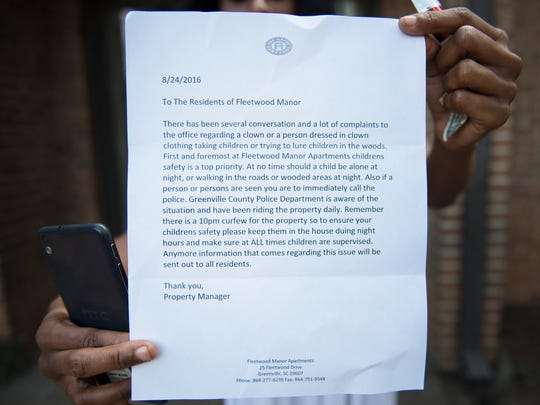 A woman holds a letter that was left by the property