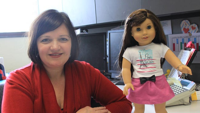 Dawn Bowlus, director of the University of Iowa's Jacobson Institute for Youth Entrepreneurship, poses Feb. 10 with the latest American Girl Doll and book. Bowlus helped provide information for the doll's entrepreneurial backstory.