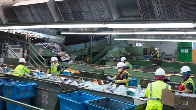 Workers at the City of Phoenix Recycling Transfer Station sort through recycled goods on June 21, 2018.