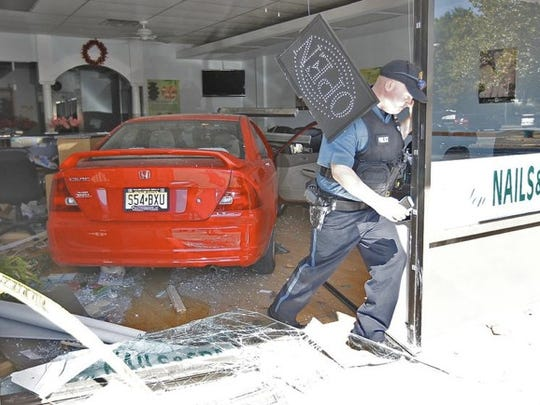 A Ramapo Police officer exits the Golden Nails & Spa in Sloatsburg after inspecting the car which drove through the window on Sunday, Sept. 7, 2014.