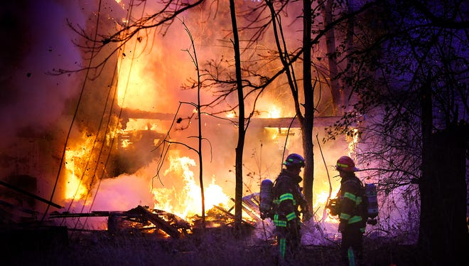 Firefighters respond to a house fire at 32247 County Road 1 south of Heim's Mill in Sartell Friday evening. Neighbors said that nobody had lived in the home for about five years.