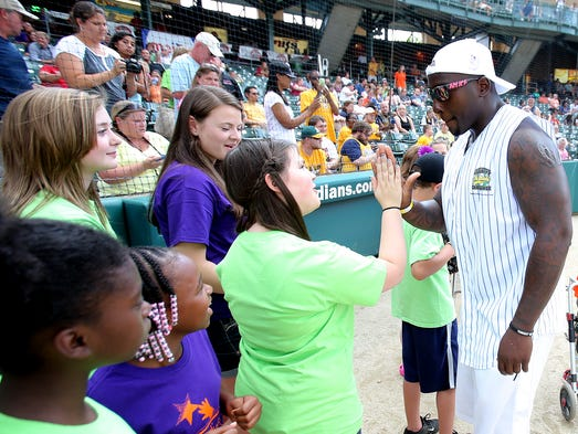 Indianapolis Colts linebacker Robert Mathis greets kids from the Indiana Children's Wish Fund during the sixth annual Caroline Symmes Memorial Celebrity Softball Challenge at Victory Field, Thursday, June 26, 2014, in Indianapolis. The event benefits the Indiana Children's Wish Fund.