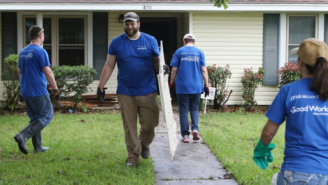 Andrew Hubenthal carries pieces of sheetrock to a pile of debris on the curb outside a home on Bennett Lake Road on Wednesday. About 50 Chase Bank employees volunteered to remove debris from houses that were flooded as part of the Chase Day of Caring. The United Way of Northeast Louisiana helped organized the day so Chase Bank could work with Samaritan's Purse to contribute to flood relief efforts.