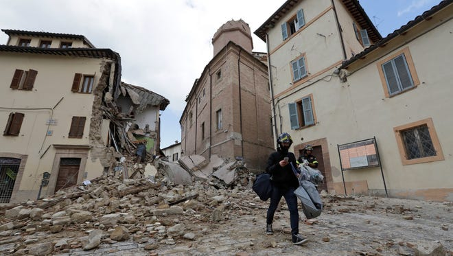 A resident carrying his belongings passes in front of the collapsed bell tower of the Santa Maria in Via church in the town of Camerino, in central Italy, Thursday, Oct 27, 2016, after a 5.9 earthquake destroyed part of the town.