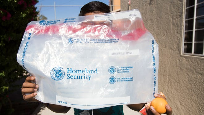 """Alfredo"", a minor who attempted to enter the U.S. without proper documentation was detained by Customs and Border Patrol and repatriated to Mexicali, Mexico. In this photo he holds up a plastic bag used by the Department of Homeland Security to hold belongings during his detainment."
