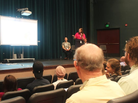 Julianna Dubin, an AmeriCorps member, presents during a keynote speech on refugee issues at the Eastern Iowa Refugee Summit at West High in Iowa City on June 16, 2017.