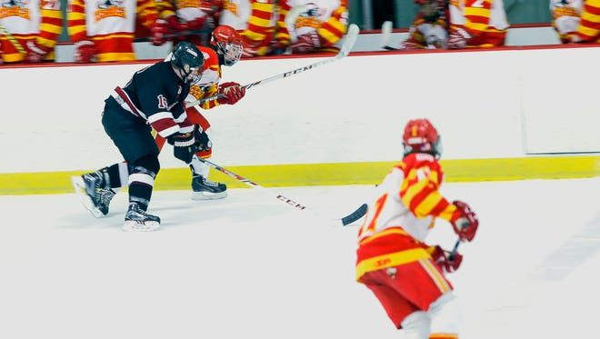 Ithaca's Aidan Evans pushes the puck up the ice with Syracuse's Andrew Hodgens in close pursuit. Syracuse, which combines players from nine different high schools, won, 6-2