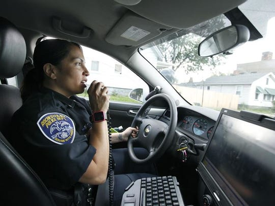 Officer Michelle Calderon answers a call while driving through the inner city in Rochester.