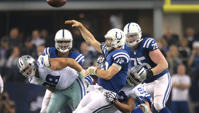 Indianapolis Colts quarterback Andrew Luck gets a pass off as he is hit by Dallas Cowboys defensive end Anthony Spencer in the second half. Indianapolis traveled to Dallas for an afternoon game Sunday, December 21, 2014.