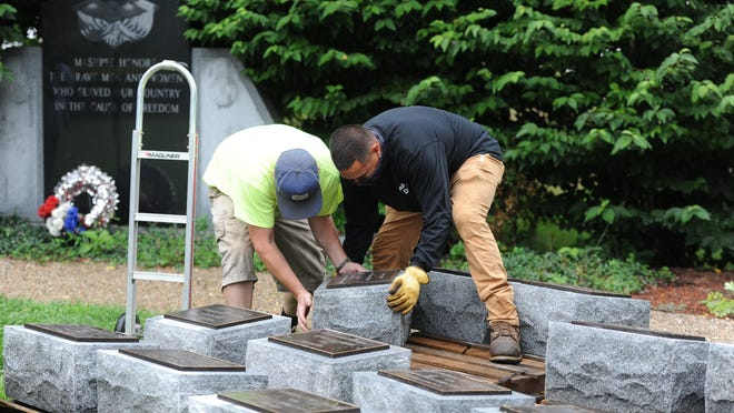 Scott Auvil, left, and Stanley Pells, both of the Mashpee Department of Public Works, place an honor stone on a dolly to move it to its spot in the Veterans Garden. Memorial stones honoring town residents who have died through the centuries in military service were installed in the park across from Town Hall on Thursday.