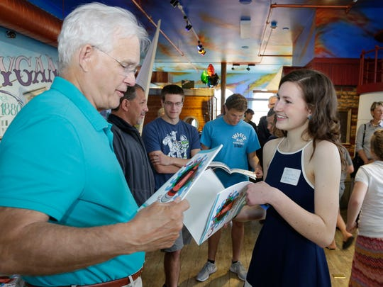 """Tom Peneski, of Sheboygan, left, gets an autographed copy of """"Color Me Sheboygan""""  by author Katie English during the premier of the book Wednesday May 31, 2017 at the Above and Beyond Children's Museum in Sheboygan, Wis."""
