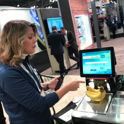 Laura Martin of NCR demonstrates a self-checkout scanner