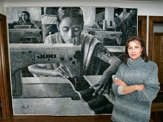 """Terese Agnew is shown in 2006 with her quilt """"Portrait of a Textile Worker,"""" which made out of garment labels."""