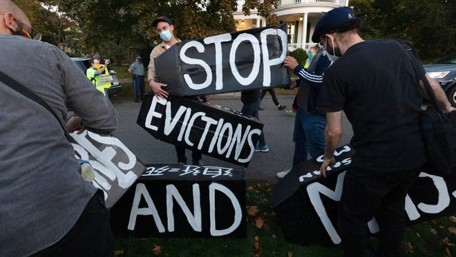 Housing activists erect a sign in front of Massachusetts Gov. Charlie Baker's house, Wednesday, Oct. 14, 2020, in Swampscott, Mass. The protesters were calling on the governor to support more robust protections against evictions and foreclosures during the ongoing coronavirus pandemic.