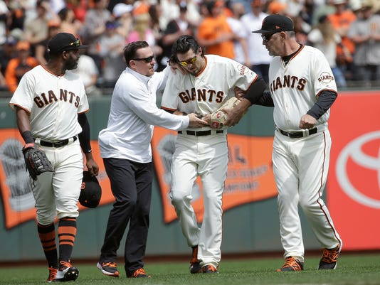 San Francisco Giants left fielder Jarrett Parker, second from right, walks off the field with center fielder Denard Span, from left, trainer Dave Groeschner and manager Bruce Bochy after catching a fly ball hit by Colorado Rockies' DJ LeMahieu during the fourth inning of a baseball game in San Francisco, Saturday, April 15, 2017. Parker was injured on the play and left the game. (AP Photo/Jeff Chiu)