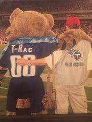 "Pete Nelson, early in his career as the Titans' mascot, ""T-Rac,"" and his father Larry Nelson watch a night game together from the sideline in Nashville."