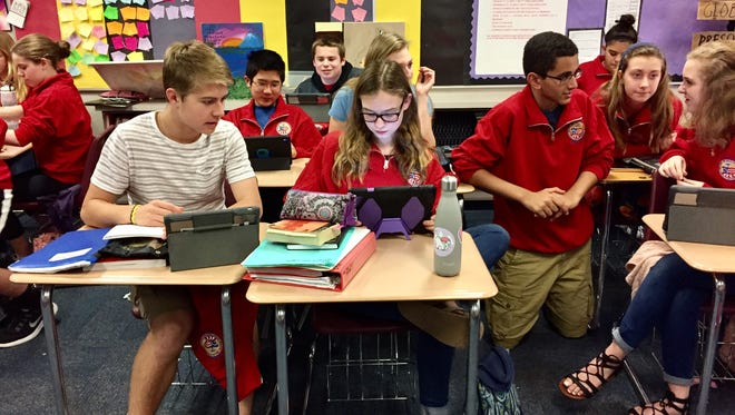 Eighth graders in Mike Fassold's civics class pick out questions from their competition list that they think would puzzle adults on April 17 in Fishers Junior High.