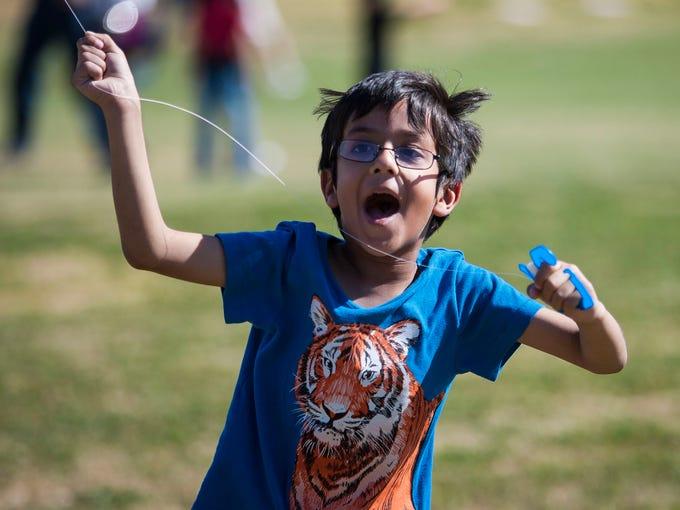 Faizan Afzal, 6, runs with his kite at the Annual Kite