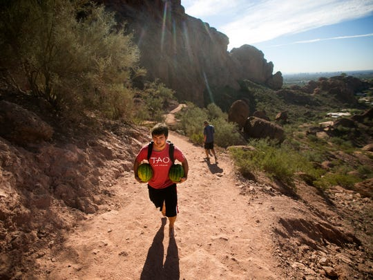 Barefoot and carrying two watermelons, Jamie Trufin, 17, of Phoenix, hikes up the Echo Canyon trail on Camelback Mountain in Phoenix on Wednesday, Nov. 19, 2014.